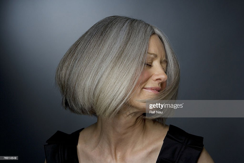 Mature woman turning head, eyes closed, close-up : Stock Photo