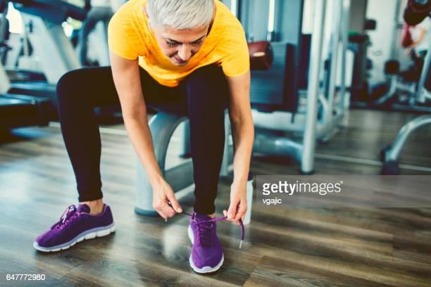 Mature Woman tying sports shoe