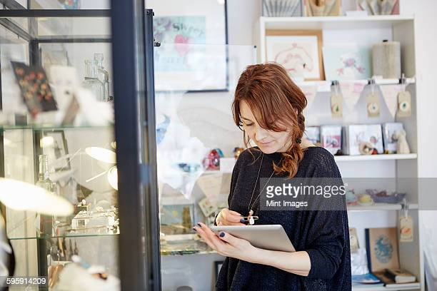 A mature woman using a digital tablet, using the touch screen, stock-taking in a small gift shop.