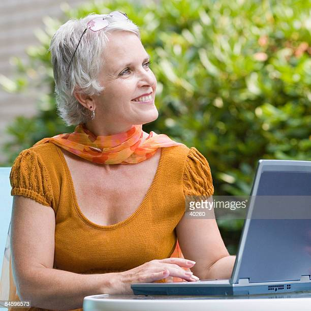 Mature woman using a laptop and smiling