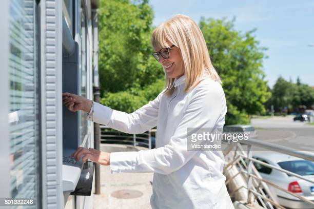 Femme mûre à l'aide de guichet automatique
