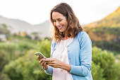 Mature happy woman using cellphone at park. Smiling woman reading message on smartphone. Brunette latin woman typing a message on her telephone after receiving an email.