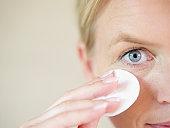 Mature woman using cotton pad, close up
