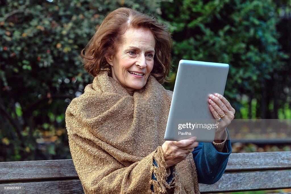Mature woman using digital tablet : Stock Photo