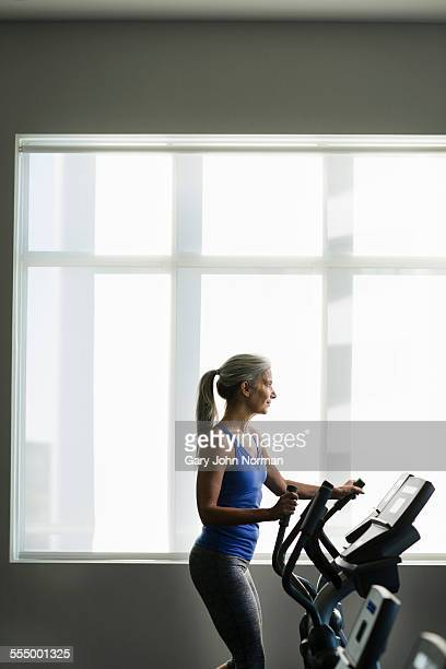Mature woman using gym step machine