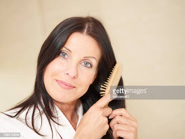 Mature woman using hair brush, smiling, portrait