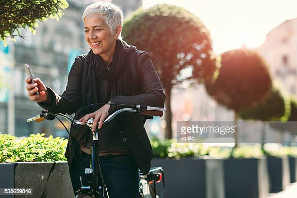 Matura donna che usa il suo smartphone in bicicletta.