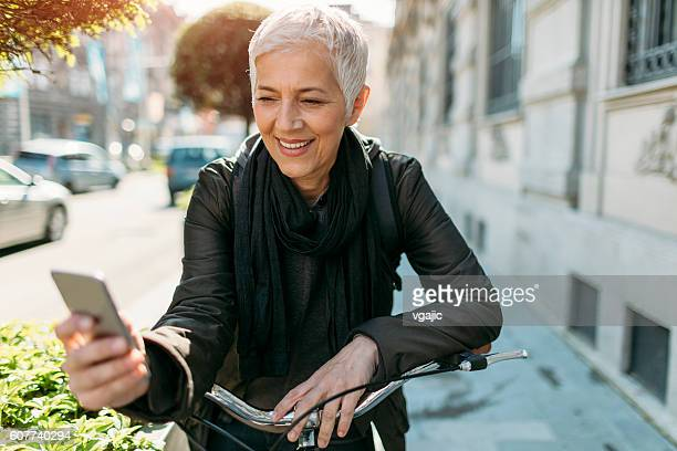 Mature Woman Using Her Smart Phone On Bicycle.