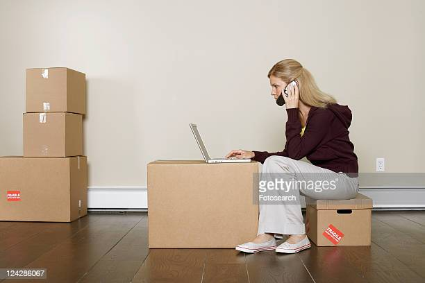 Mature woman using laptop and mobile phone on cardboard box