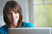 Mature woman using laptop and telephone headset