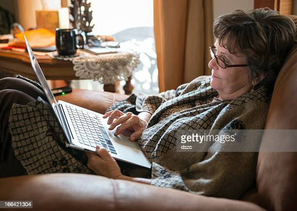 mature woman using laptop computer while sitting in comfortable chair