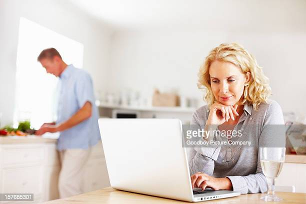 Mature woman using laptop while man cooking in kitchen