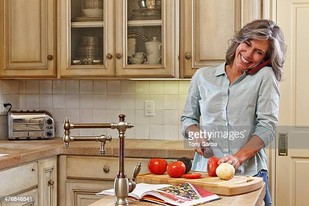 Mature woman using mobile and preparing food in kitchen