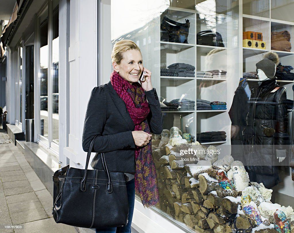 mature woman using smart phone, window shopping : Stock Photo