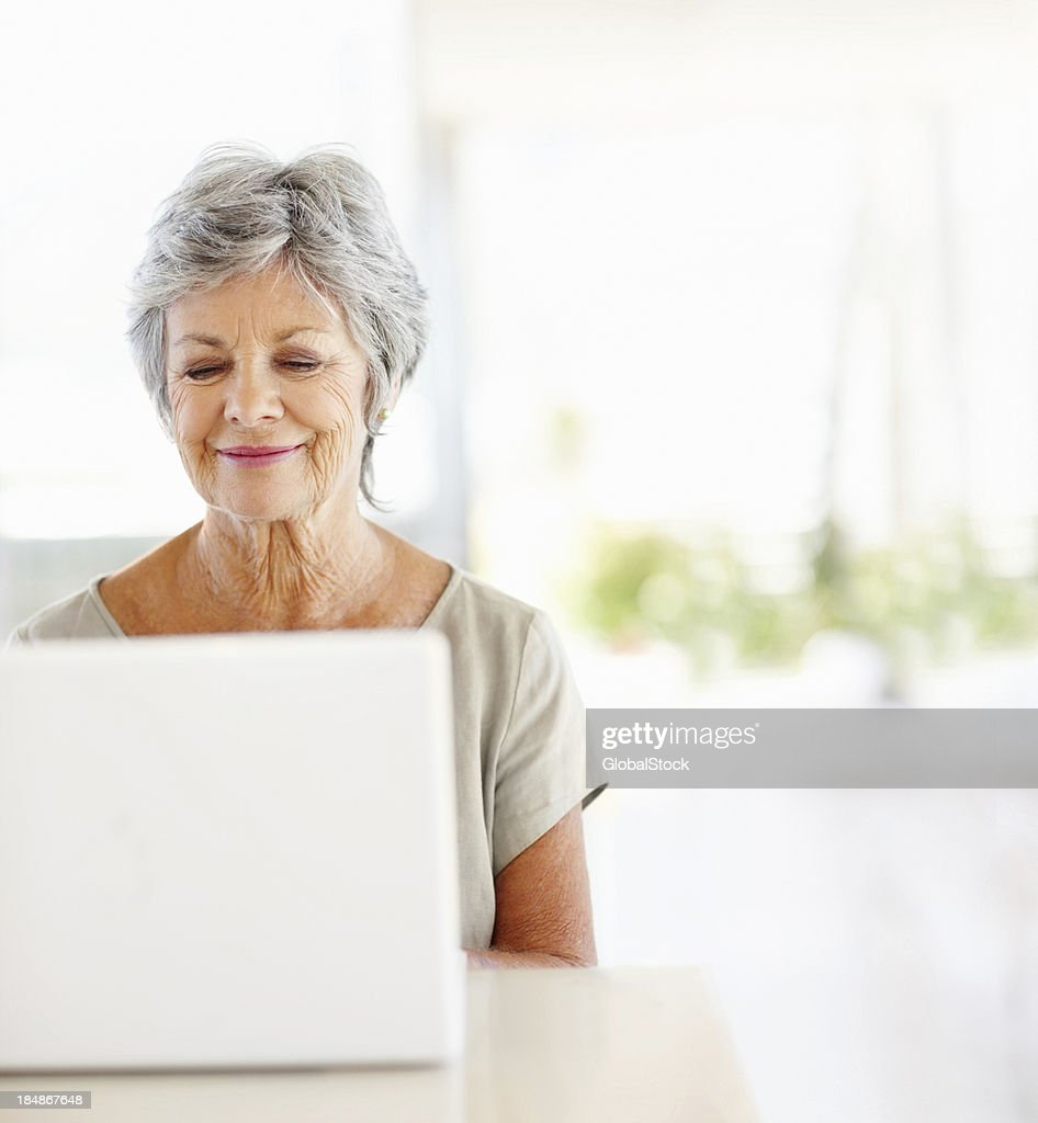 Mature woman using the internet : Stock Photo