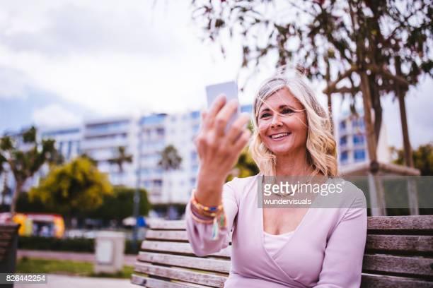 Reife Frau-Videoanrufe auf ihrem Smartphone in der Stadt