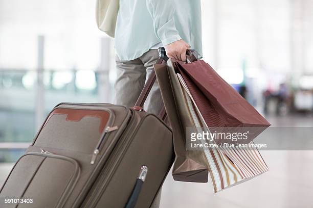 Mature woman waiting at airport with shopping bags