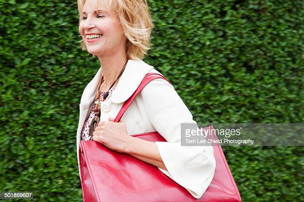 Mature woman walking briskly with red shoulder bag