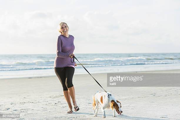 Mature woman walking dog on beach