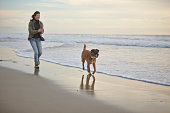 Mature woman walking dog on breezy beach