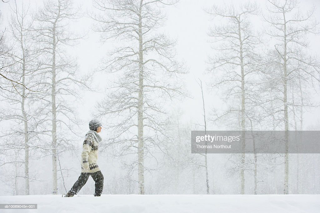 Mature woman walking in snow : Stock Photo