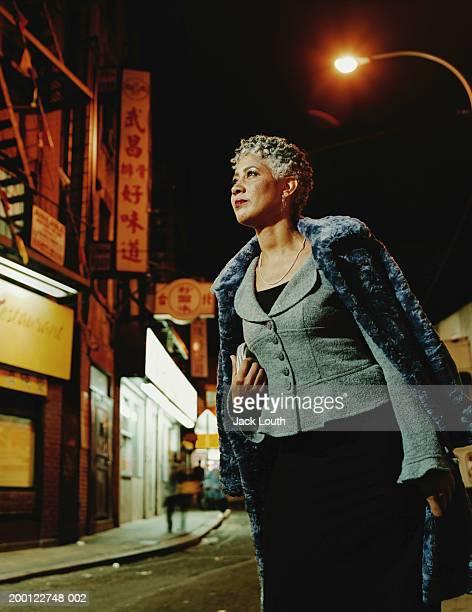 Mature woman walking in street, night