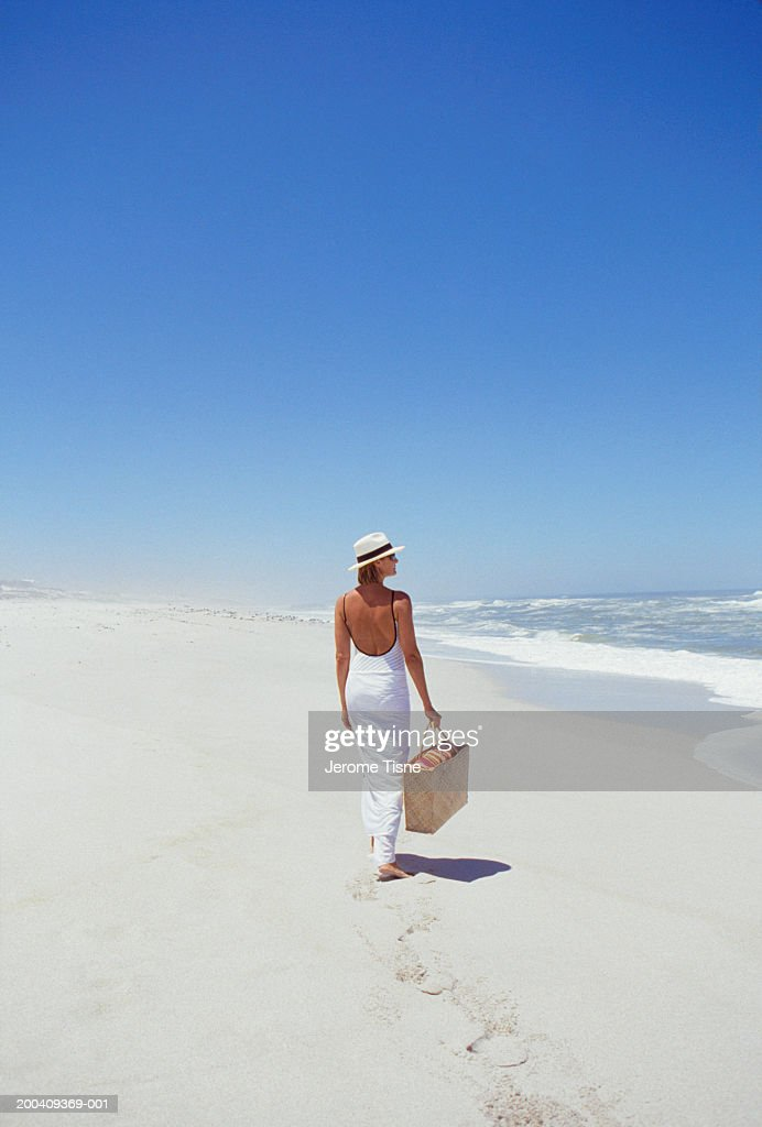 Mature woman walking on beach, rear view : Stock Photo