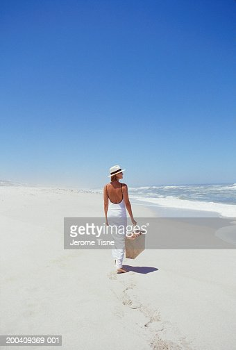 Mature woman walking on beach, rear view : Foto de stock