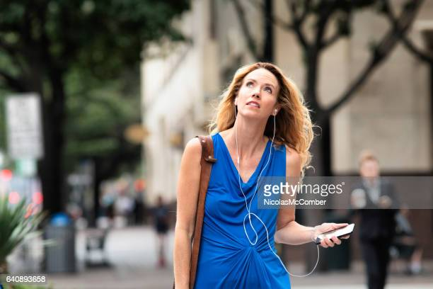 Mature woman walking to work worrying about weather.