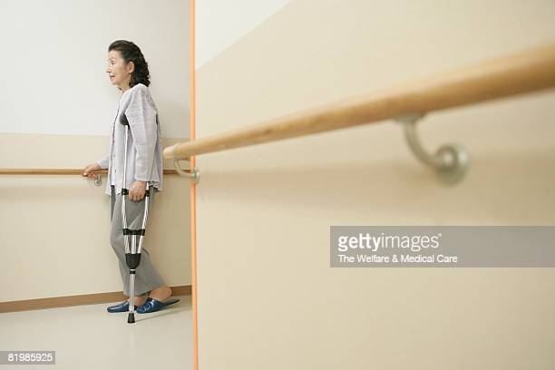 Mature woman walking with crutch