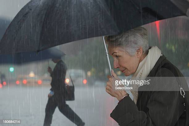 Mature woman walking with umbrella