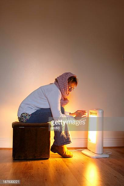 Mature woman warming hands by glow of halogen lamp