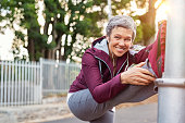 Smiling retired woman listening to music while stretching legs outdoors. Senior woman enjoying daily routine warming up before running at morning. Sporty lady doing leg stretches before workout and lo