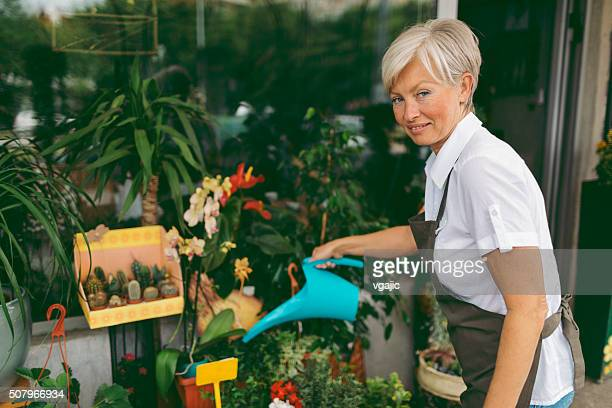 Mature woman watering flowers in flower shop