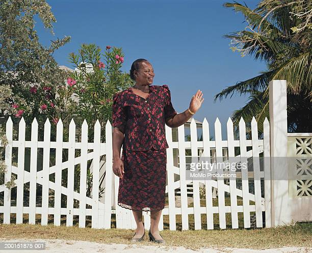 Mature woman waving in front of fence, smiling