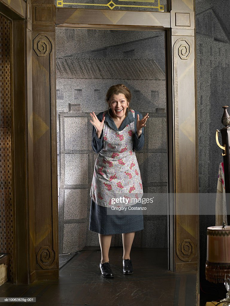 Mature woman wearing apron, standing in doorway with arms raised, portrait
