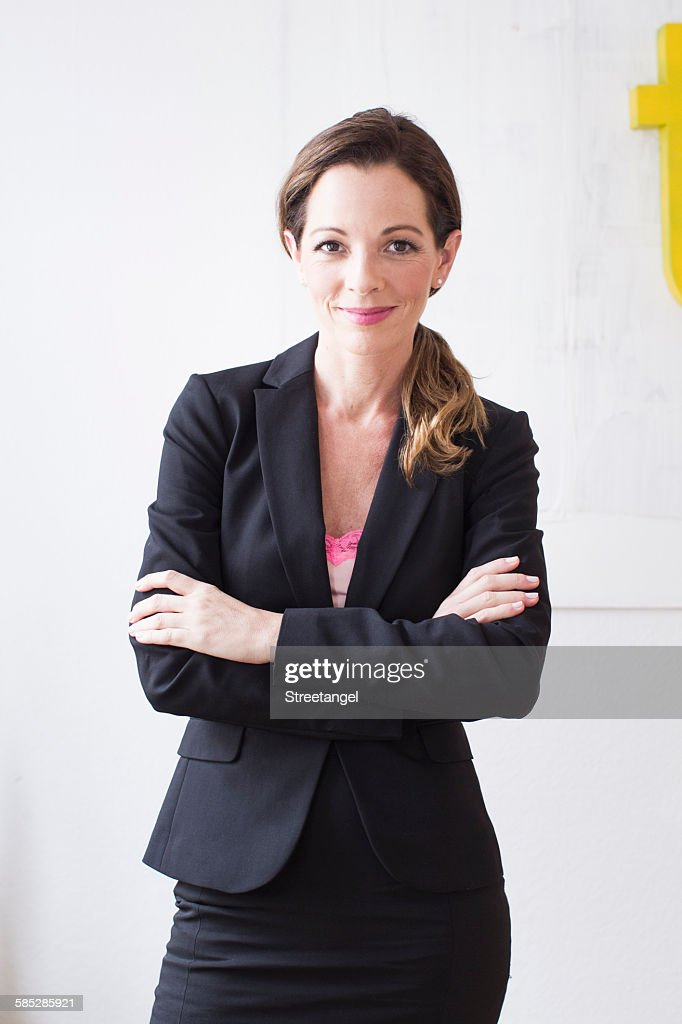 Mature woman wearing business attire arms crossed looking at camera smiling