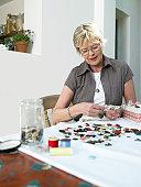 Mature woman wearing glasses, matching button to shirt