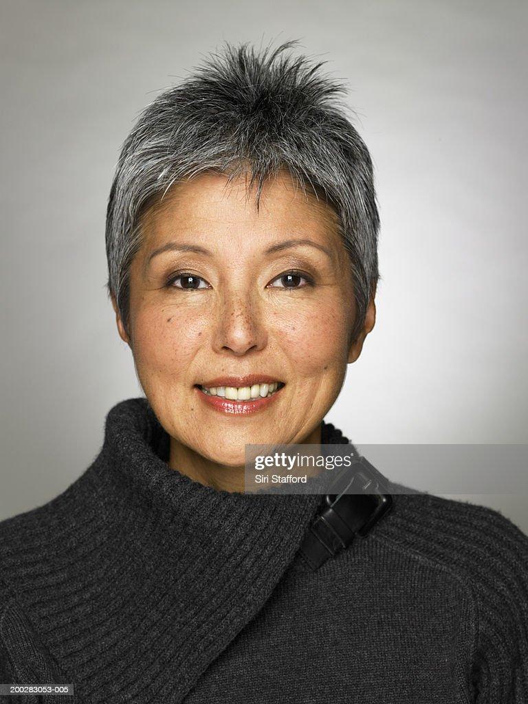 Mature woman wearing grey top, portrait : Stock Photo