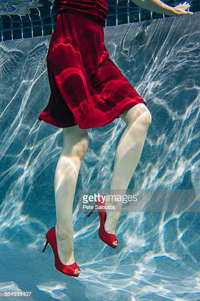 Mature woman wearing red dress and high heels, underwater view, low section