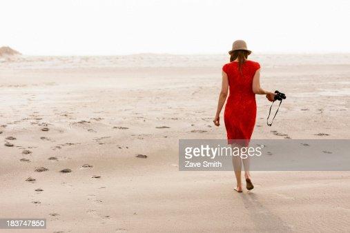 Mature woman wearing red dress walking on beach