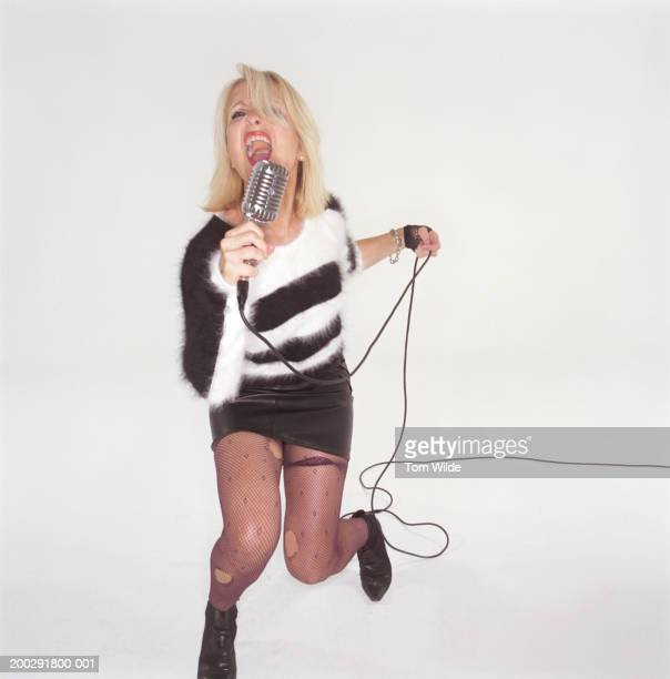 Mature woman wearing ripped tights singing into microphone