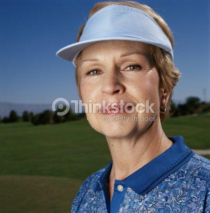 60cd9729 Mature woman wearing sun visor, high section, portrait : Stock Photo