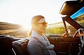 Mature woman wearing sunglasses driving at sunset