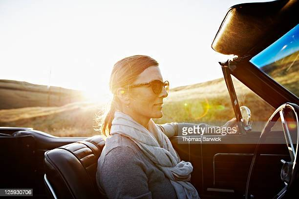 Mature woman wearing sunglasses driving at sunset