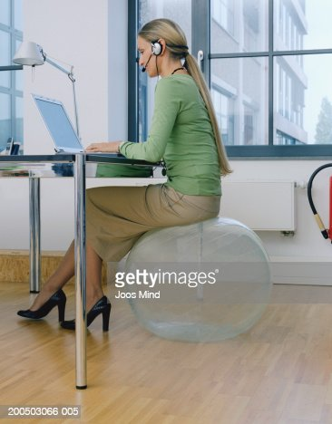 Mature woman wearing telephone headset in office using laptop : Stock Photo