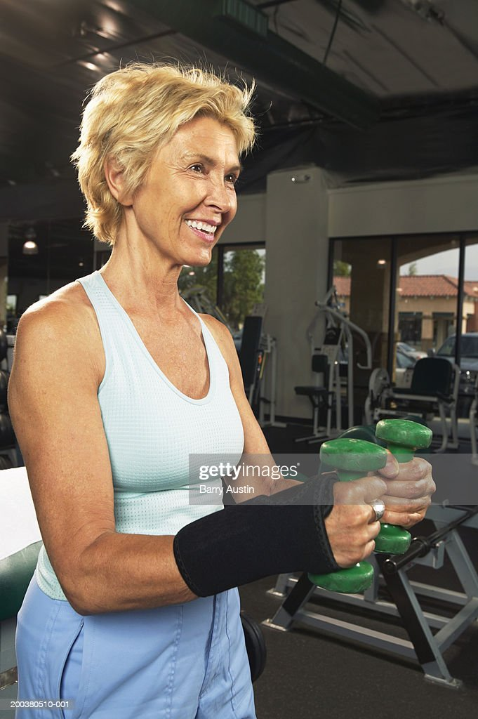 Mature woman weight training in gym, smiling : Stock Photo