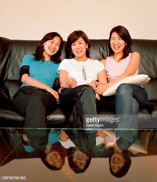 Mature woman with adult daughters laughing on sofa