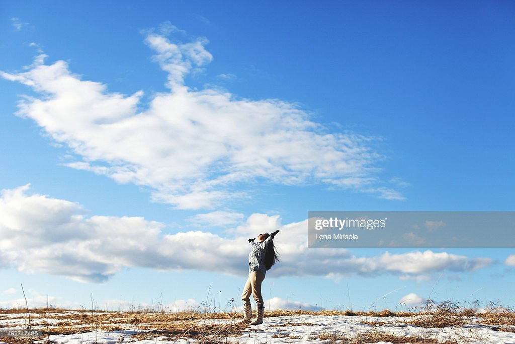 Mature woman with arms outstretched in landscape : Stock Photo