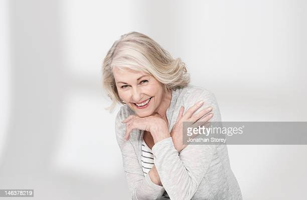 Mature woman with arms resting on hand laughing